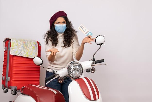 Vooraanzicht jonge vrouw met fietsticket op een witte achtergrondkleur covid- voertuigvirus pandemische motorfiets snelheidsvlucht