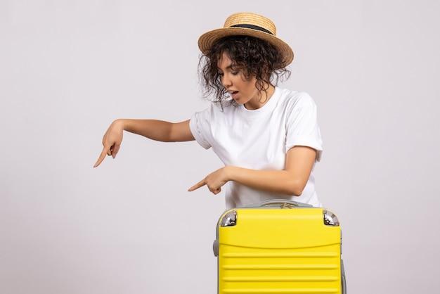 Vooraanzicht jonge vrouw met gele tas die zich voorbereidt op een reis op een witte achtergrond vakantie vliegtuig reis kleur rust vluchten toerist