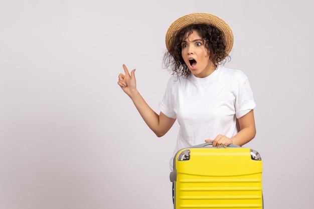 Vooraanzicht jonge vrouw met gele tas die zich voorbereidt op reis geschokt op de witte achtergrond vlucht rust reis toeristische vakantie kleur vliegtuig zon