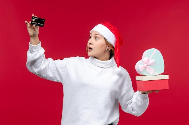 Vooraanzicht jonge vrouw met geschenken en bankkaart op de rode achtergrond