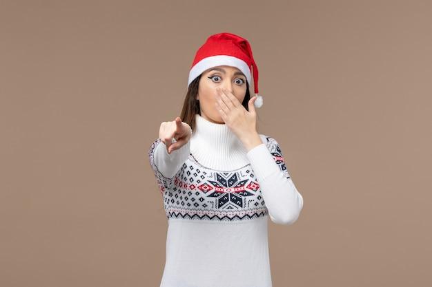 Vooraanzicht jonge vrouw met geschokte uitdrukking op bruine achtergrond nieuwe jaar emotie kerstmis