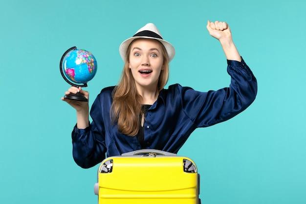 Vooraanzicht jonge vrouw met globe en voorbereiding op vakantie op blauwe achtergrond vrouwelijke reis reis watervliegtuig vakantie
