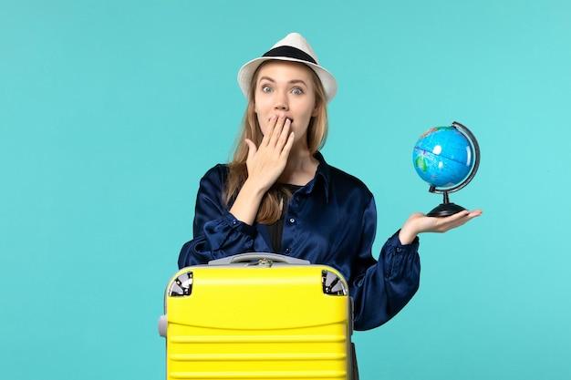 Vooraanzicht jonge vrouw met globe en voorbereiding op vakantie op lichtblauwe achtergrond vrouwelijke vakantie reis reis watervliegtuig