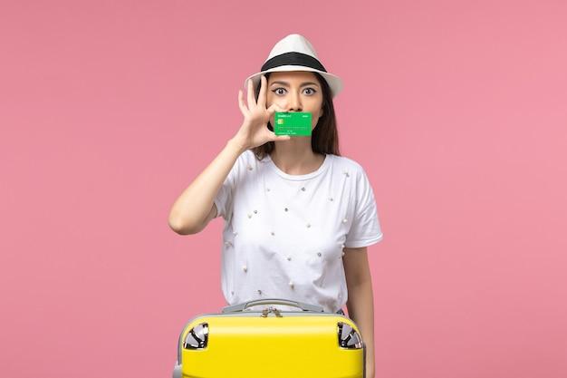 Vooraanzicht jonge vrouw met groene bankkaart op de roze muur emoties zomer vrouw trip