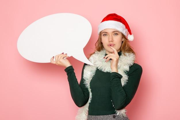 Vooraanzicht jonge vrouw met groot wit bord op roze muur kerst nieuwjaar model vakantie kleur emoties