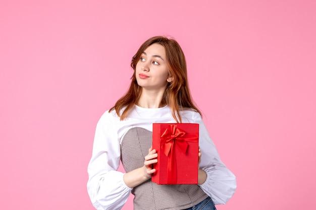 Vooraanzicht jonge vrouw met heden in rood pakket op roze achtergrond liefde datum maart horizontaal geschenk parfum vrouw foto geldgelijkheid