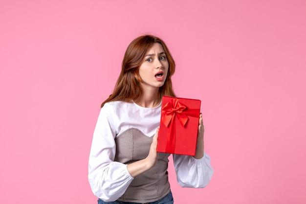 Vooraanzicht jonge vrouw met heden in rood pakket op roze achtergrond maart geld horizontale sensuele gelijkheid vrouw geschenken