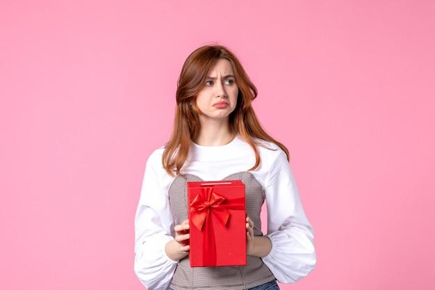 Vooraanzicht jonge vrouw met heden in rood pakket op roze achtergrond maart horizontale sensuele cadeau parfum foto gelijkheid vrouw