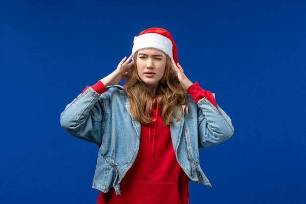 Vooraanzicht jonge vrouw met hoofdpijn op blauwe achtergrond kerst emotie kleur