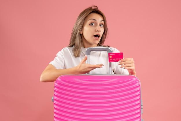 Vooraanzicht jonge vrouw met kaart achter grote koffer
