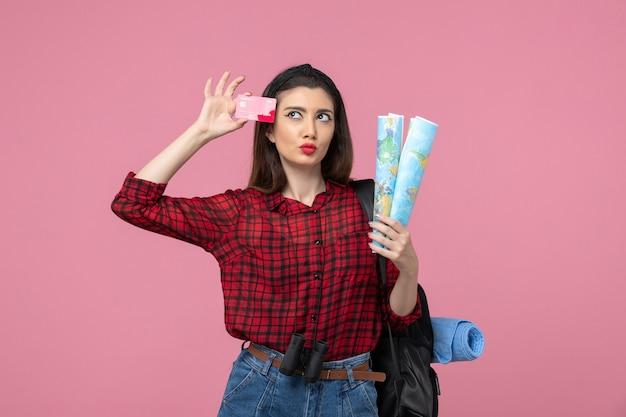 Vooraanzicht jonge vrouw met kaarten en bankkaart op de roze achtergrondkleur vrouw mens