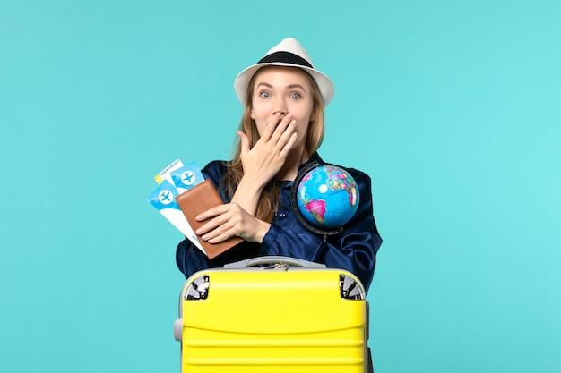 Vooraanzicht jonge vrouw met kaartjes en globe op lichtblauwe achtergrond vliegtuig reis zee vakantie reis