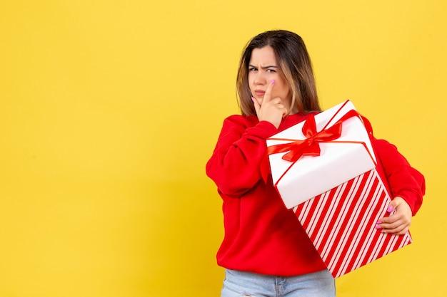 Vooraanzicht jonge vrouw met kerst cadeau denken op gele achtergrond