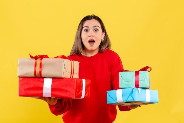 Vooraanzicht jonge vrouw met kerstcadeaus op geel bureau