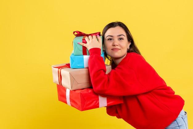 Vooraanzicht jonge vrouw met kerstcadeaus op gele achtergrond Gratis Foto