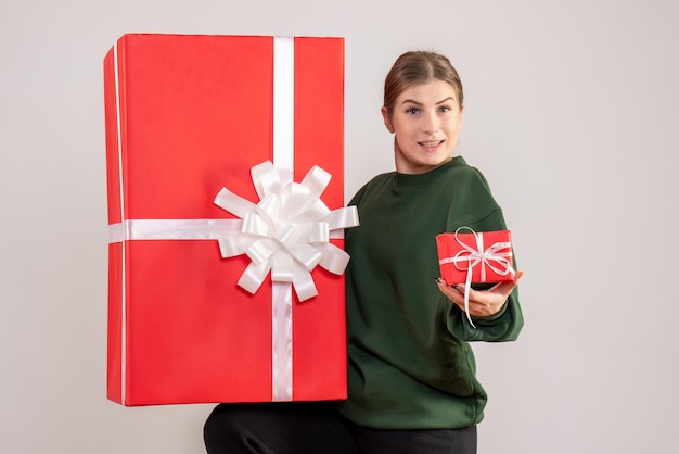 Vooraanzicht jonge vrouw met kleine en enorme kerstcadeautjes
