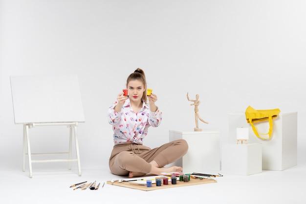 Vooraanzicht jonge vrouw met kleurrijke verf in blikjes op witte achtergrond