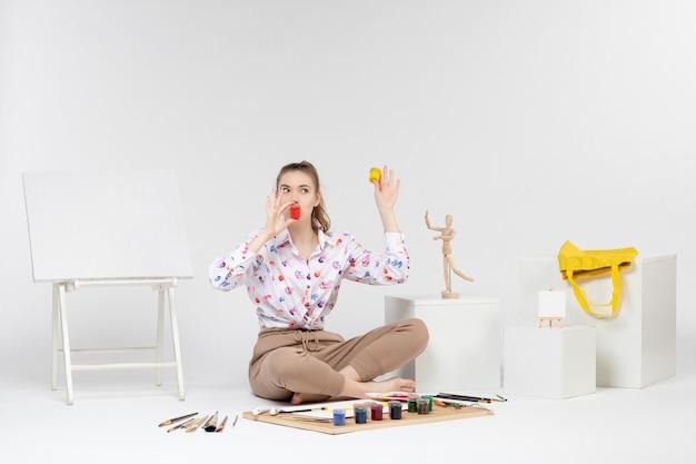 Vooraanzicht jonge vrouw met kleurrijke verf in kleine blikjes op witte achtergrond