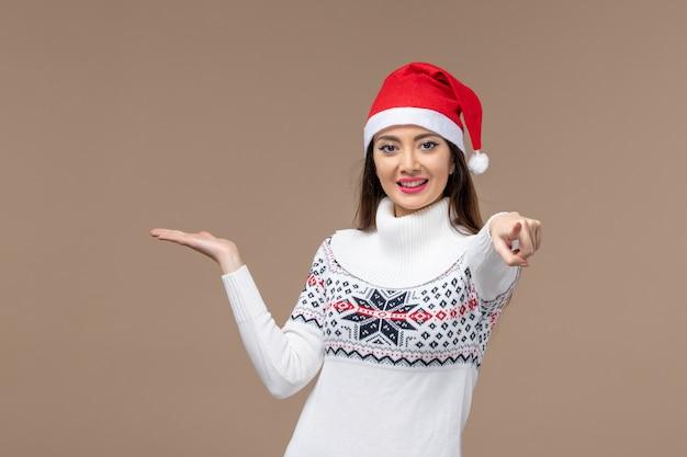 Vooraanzicht jonge vrouw met lachende uitdrukking op bruine achtergrond vakantie emotie kerst