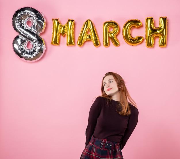 Vooraanzicht jonge vrouw met maart decoratie op roze achtergrond cadeau gelijkheid vrouw passie dames dag huwelijk sensuele aanwezig