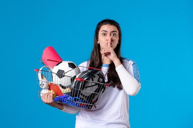 Vooraanzicht jonge vrouw met mand vol sport dingen blauwe muur