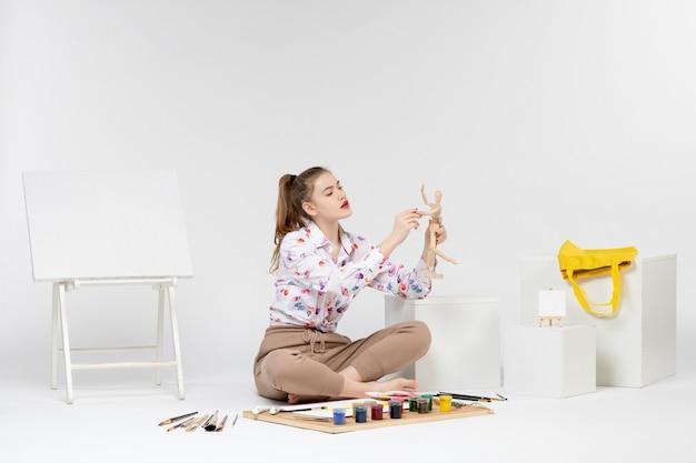 Vooraanzicht jonge vrouw met menselijke figuur op witte achtergrond