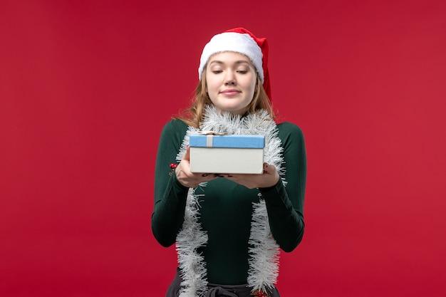 Vooraanzicht jonge vrouw met nieuw jaar aanwezig op rode achtergrond