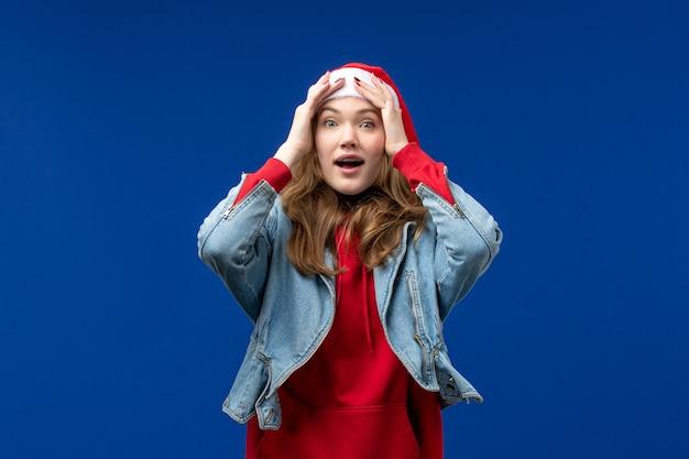 Vooraanzicht jonge vrouw met opgewonden uitdrukking op blauwe achtergrond kerst emotie kleur