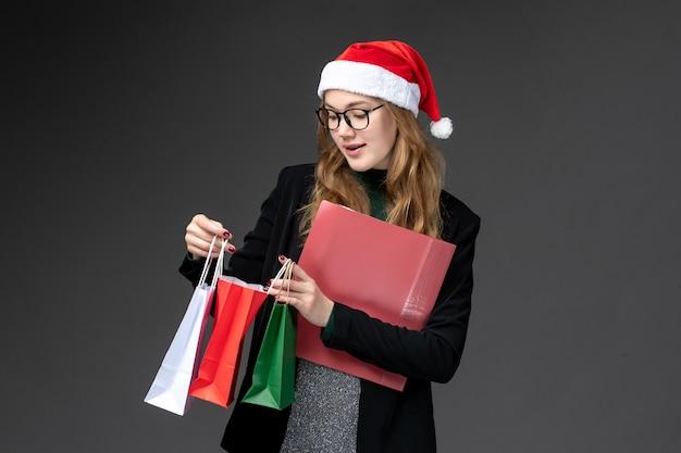 Vooraanzicht jonge vrouw met pakketten op donkere muur cadeau nieuwjaar kerstcadeautjes