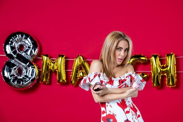Vooraanzicht jonge vrouw met poederdoos op maart ingericht rode achtergrond wimper huid horizontale make-up glamour schoonheid huidverzorging glans