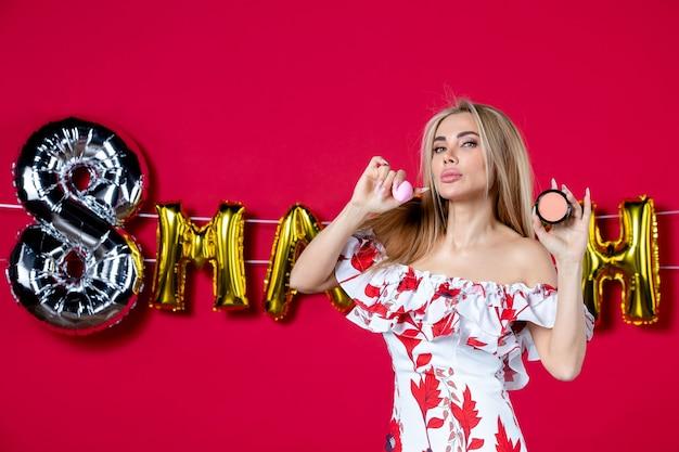 Vooraanzicht jonge vrouw met poederdoos op maart ingericht rode achtergrond wimper huid make-up glamour schoonheid huidverzorging horizontaal