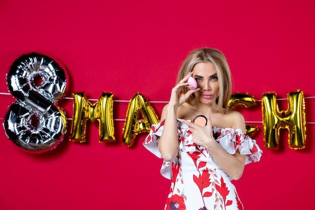 Vooraanzicht jonge vrouw met poederdoos op maart ingericht rode achtergrond wimper huid make-up schoonheid huidverzorging glans horizontale glamour kleur