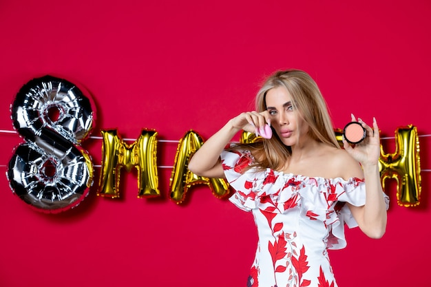 Vooraanzicht jonge vrouw met poederdoos op maart ingericht rode achtergrond wimper huid make-up schoonheid huidverzorging glans horizontale glamour