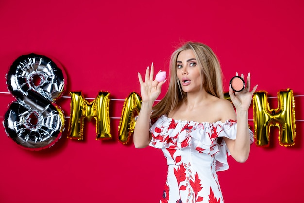 Vooraanzicht jonge vrouw met poederdoos op maart verfraaide rode achtergrond wimper huid make-up glamour huidverzorging glans horizontaal
