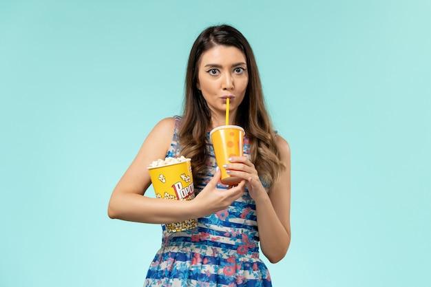 Vooraanzicht jonge vrouw met popcorn en drankje op het blauwe oppervlak