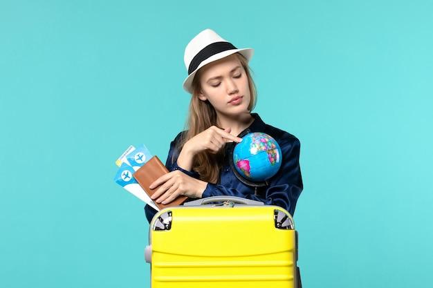 Vooraanzicht jonge vrouw met portemonnee met kaartjes op blauwe vloer vliegtuig reis vrouw reis zee vakantie