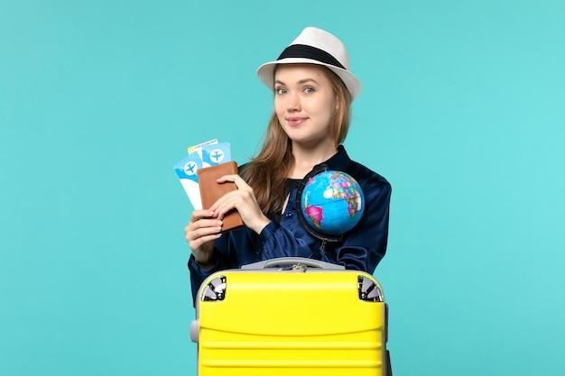 Vooraanzicht jonge vrouw met portemonnee met kaartjes op de blauwe achtergrond vliegtuig reis vrouw reis zee vakantie