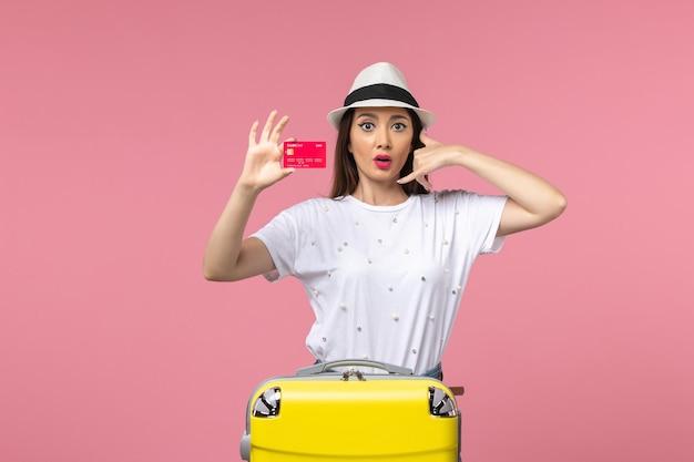 Vooraanzicht jonge vrouw met rode bankkaart op de roze muur zomerreis reis