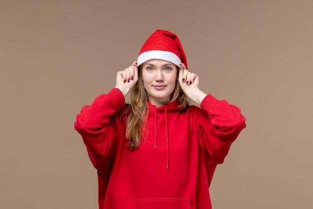 Vooraanzicht jonge vrouw met rode cape lachend op bruine achtergrond kerst emotie vakantie