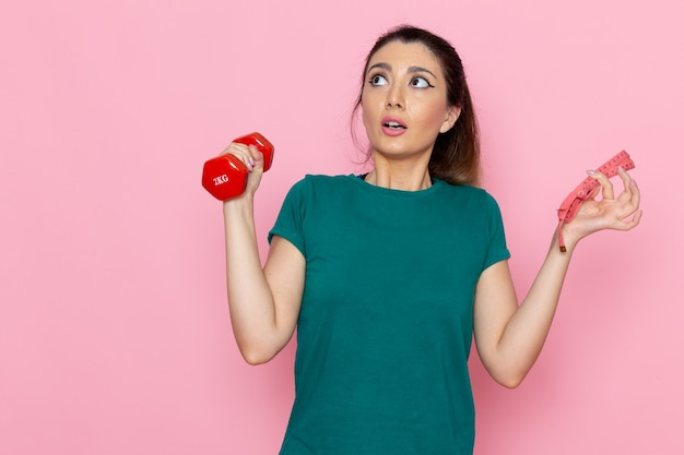 Vooraanzicht jonge vrouw met rode halters op de lichtroze muur atleet sport oefening gezondheid trainingen