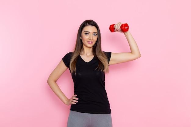 Vooraanzicht jonge vrouw met rode halters op lichtroze bureau atleet sport oefening gezondheid trainingen