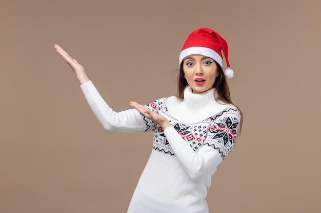 Vooraanzicht jonge vrouw met rode kerst dop op bruine achtergrond kerst emoties nieuwjaar