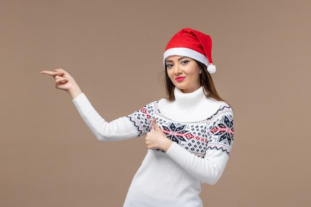 Vooraanzicht jonge vrouw met rode kerst pet op bruine achtergrond emotie kerst nieuwjaar