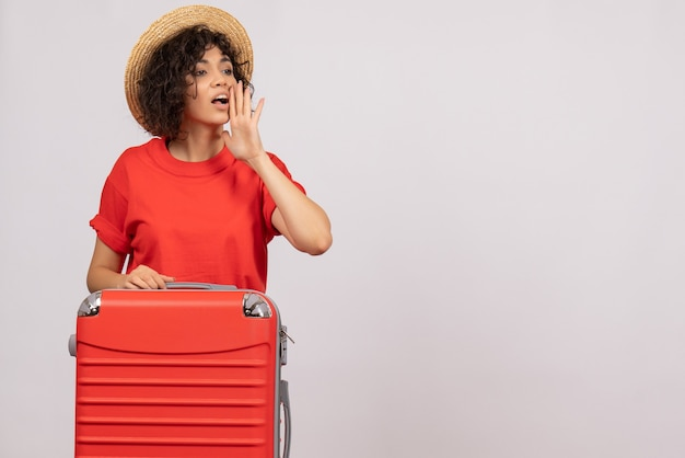 Vooraanzicht jonge vrouw met rode tas die zich voorbereidt op een reis op een witte achtergrond vlucht kleur vliegtuig rust zon toeristische reis vakantie
