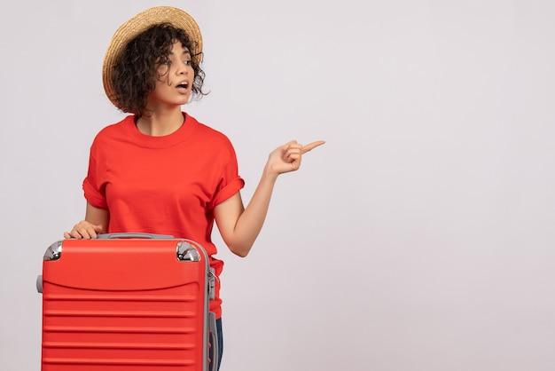 Vooraanzicht jonge vrouw met rode tas die zich voorbereidt op een reis op een witte achtergrondkleur vliegtuig rust vakantie zon toeristische vlucht reis
