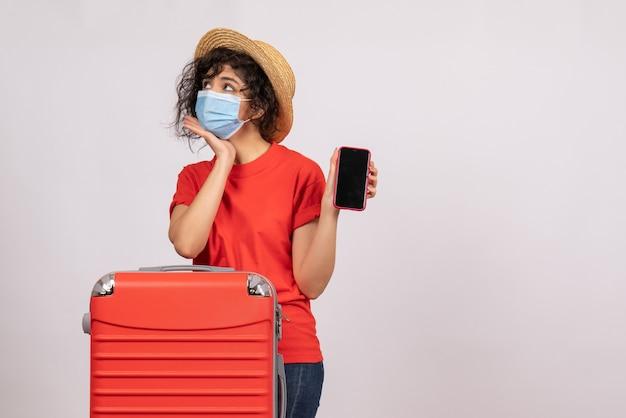 Vooraanzicht jonge vrouw met rode tas in masker met telefoon op een witte achtergrond zon covid pandemie vakantie reis toeristische virus kleur