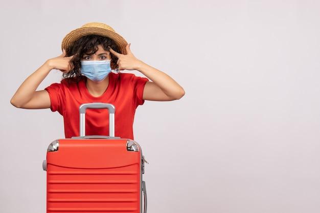 Vooraanzicht jonge vrouw met rode zak in masker op witte achtergrond zon covid pandemie vakantie reis toeristische virus kleur