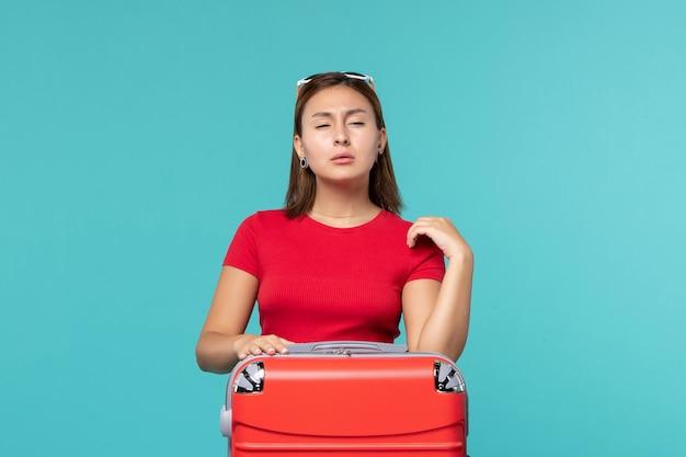 Vooraanzicht jonge vrouw met rode zak klaar voor vakantie op lichtblauwe ruimte