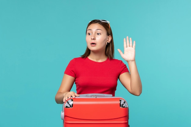 Vooraanzicht jonge vrouw met rode zak klaar voor vakantie zwaaien op blauwe ruimte
