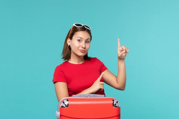 Vooraanzicht jonge vrouw met rode zak vakantie op de blauwe ruimte voorbereiden